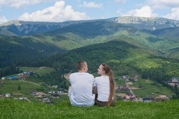 Para kochanków siedzi na wzgórzu i podziwia widok na góry. spoczywajcie razem. widok z tyłu