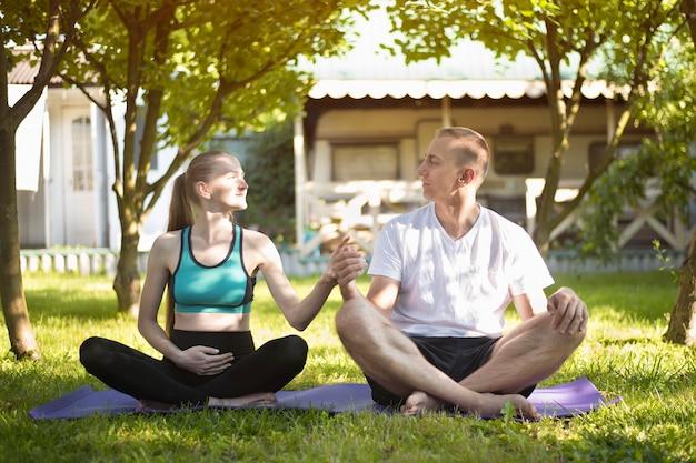 Para kochanków uprawiających jogę w ogrodzie. kobieta w ciąży. letni poranek