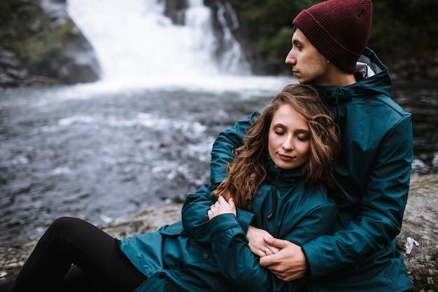 Para kochanków w zielonych płaszczach przeciwdeszczowych, siedzących na skale, na tle wodospadu