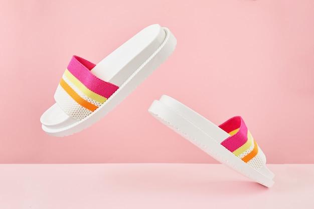 Para kolorowych wielokolorowych tęczowych klapek lub sandałów na pastelowym tle koncepcja lato