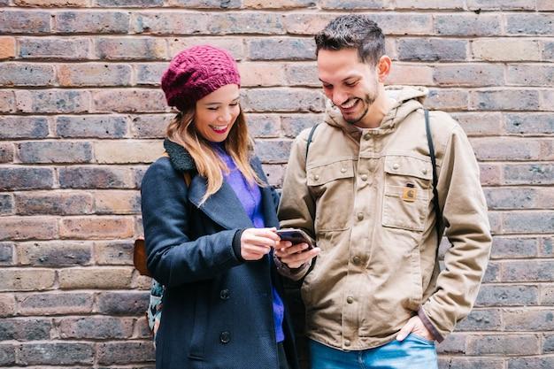 Para korzysta z telefonu komórkowego z murem w tle