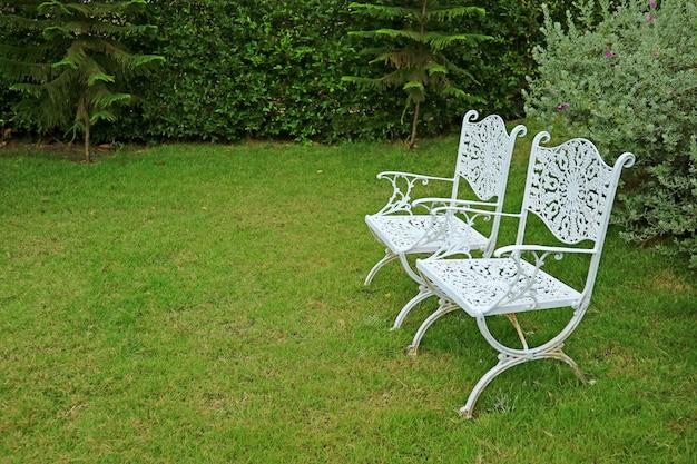 Para krzeseł kutego żelaza w stylu vintage białe kolorowe w tętniącym życiem zielonym ogrodzie