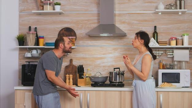 Para krzyczy na siebie rano w kuchni. młoda para kłóci się w kuchni. mężczyzna i kobieta krzyczą z frustracji podczas rozmowy domowej.