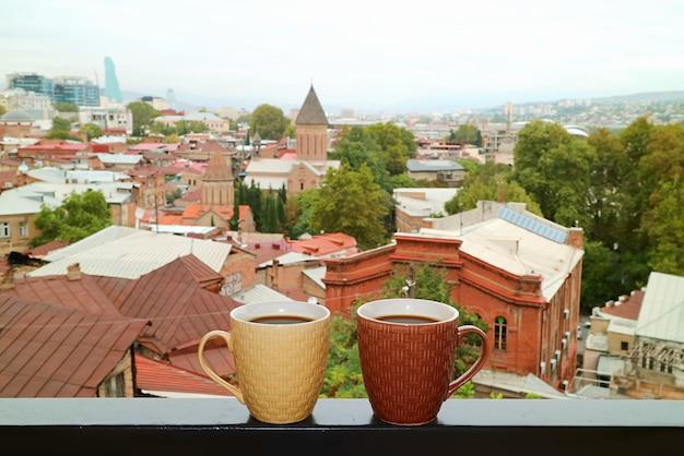 Para kubków na gorącą kawę na balustradzie balkonu z widokiem na tbilisi w tle
