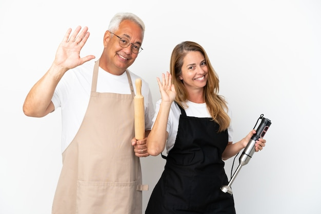 Para kucharzy w średnim wieku na białym tle pozdrawiając ręką ze szczęśliwym wyrazem twarzy