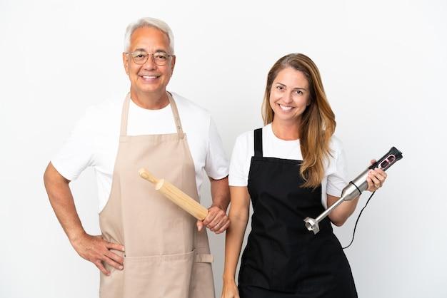 Para kucharzy w średnim wieku na białym tle pozuje z rękami na biodrach i uśmiecha się