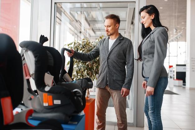 Para Kupuje Fotelik Samochodowy Dla Dziecka W Salonie. Premium Zdjęcia