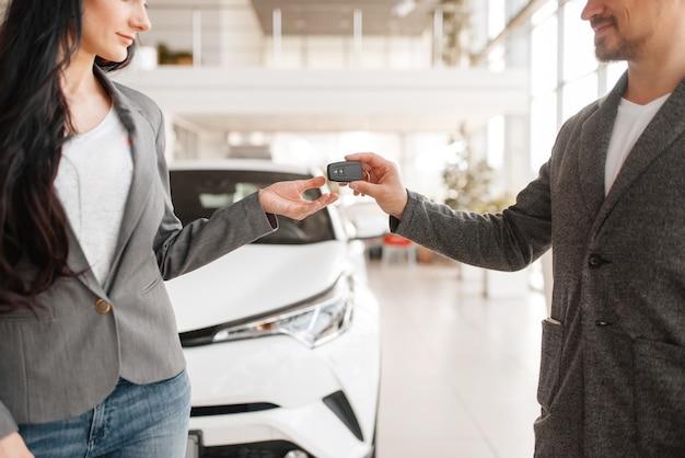 Para kupuje nowy samochód w salonie, mężczyzna daje klucz kobiecie.