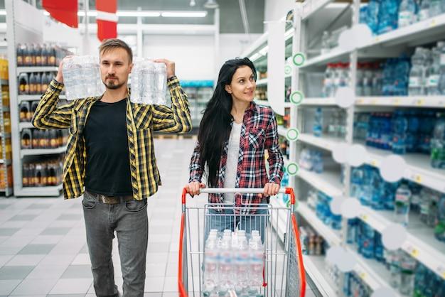 Para kupuje wodę mineralną w supermarkecie. klienci płci męskiej i żeńskiej na rodzinne zakupy. mężczyzna i kobieta kupują napoje