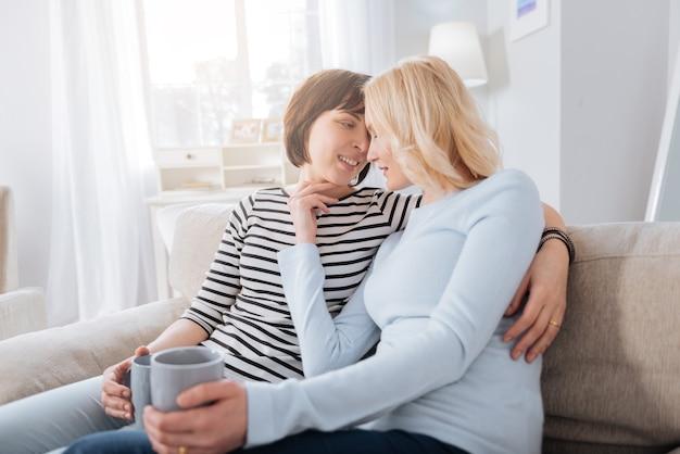 Para lesbijek. przyjemna, sympatyczna para lesbijek siedzi na sofie i pije herbatę podczas wspólnego odpoczynku