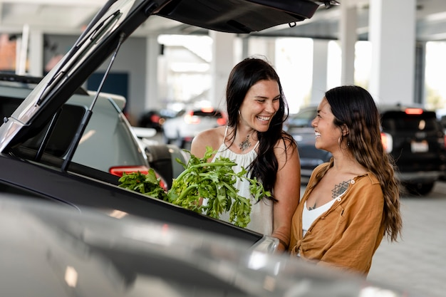 Para lesbijek robi zakupy spożywcze, wkłada rzeczy do bagażnika samochodu