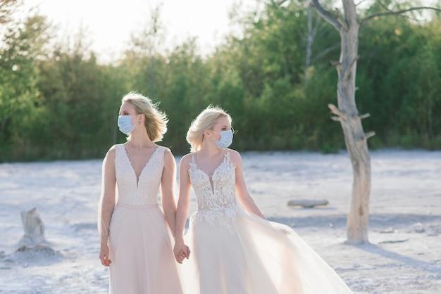 Para lesbijek ślubuje na białym piasku, noś maski, aby zapobiec epidemii covid-19