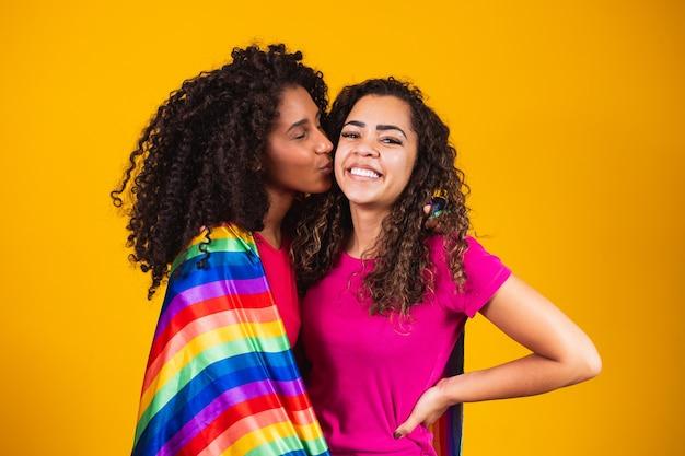 Para lesbijek z flagą dumy gejowskiej na żółtym tle