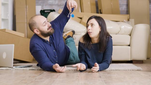Para leżąca na podłodze w swoim nowym mieszkaniu. chłopak daje klucze swojej dziewczynie.