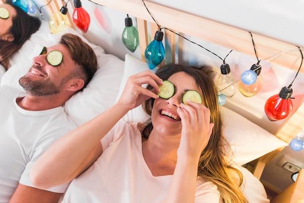 Para leżącego na łóżku z plasterkiem ogórka nad ich oczami