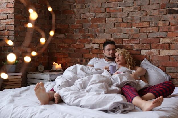 Para leży na łóżku w bliźniaczych piżamach i marzy