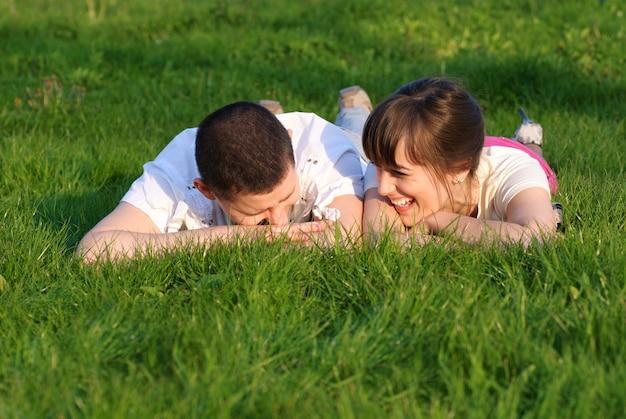 Para leży na trawie i patrzy w górę. shallow dof. portret na zewnątrz