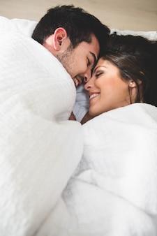 Para leży w łóżku i opakowane do szyi