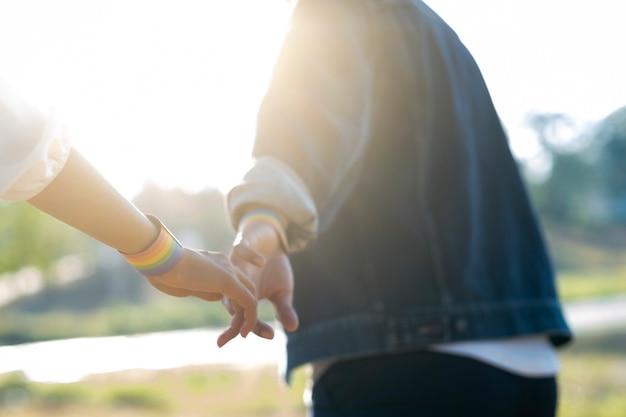 Para lgbt trzyma ręki chodzi w parku.
