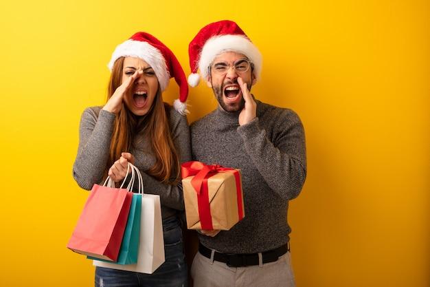Para lub przyjaciele gospodarstwa prezenty i torby na zakupy krzycząc coś szczęśliwego z przodu