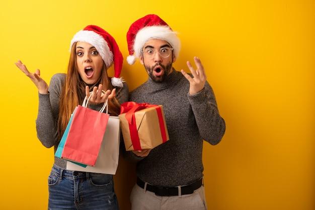 Para lub przyjaciele gospodarstwa prezenty i torby na zakupy świętuje zwycięstwo lub sukces