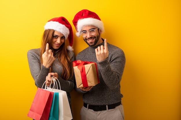Para lub przyjaciele gospodarstwa prezenty i torby na zakupy zaprasza do przyjścia