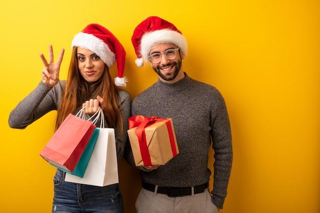 Para lub przyjaciele trzyma prezenty i torba na zakupy pokazuje liczbę trzy
