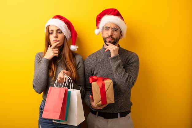 Para lub przyjaciele trzymając prezenty i torby na zakupy wątpiąc i mylić