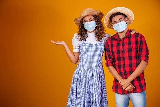 Para ma na sobie typowe ubrania na festa junina (junina party) i maskę ochronną, aby zapobiec covid-19