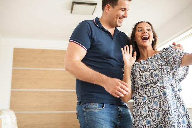 Para ma wideorozmowę ze swoim przyjacielem pokazującym nowy dom. młoda para szczęśliwa z domu