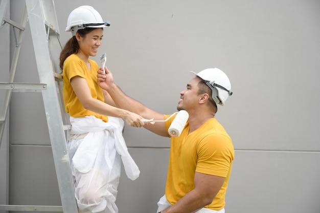 Para maluje ścianę