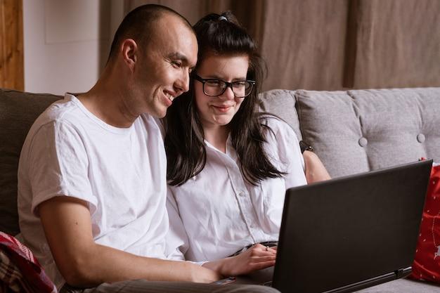Para małżeńska siedząca w domu na kanapie z laptopem zamawia towary przez internet