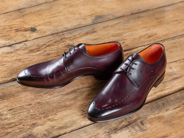 Para męskich skórzanych butów na drewnianej powierzchni z desek. widok z boku, selektywna ostrość. zbliżenie. włoski design