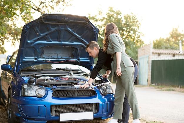Para mężczyzn i kobiet ma problemy z samochodem podczas podróży, naprawa silnika, przegląd