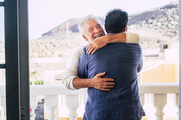 Para mężczyzn w różnym wieku, jak dorośli ojciec i syn, przytulają się z miłością i relacją rodzinną na świeżym powietrzu na tarasie w domu