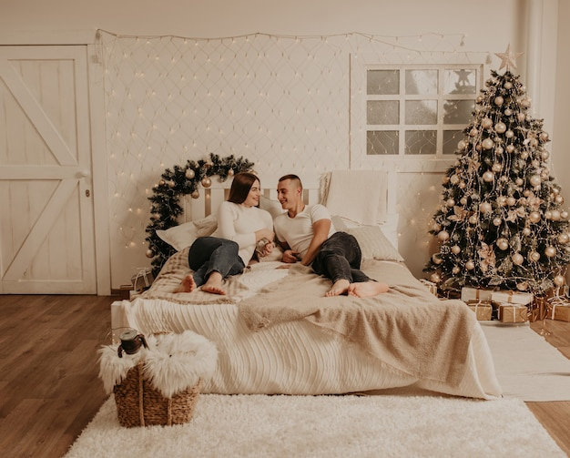 Para mężczyzna i kobieta leżą w sypialni w pobliżu choinki. ozdobiony dom na nowy rok