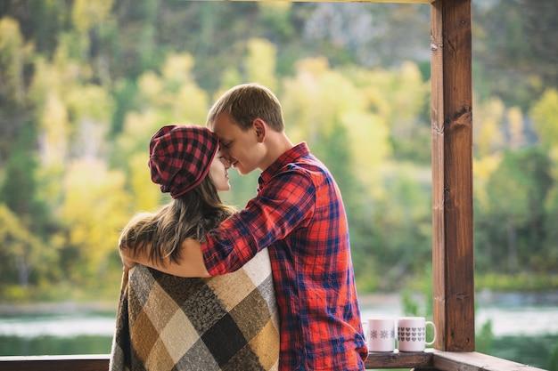 Para mężczyzna i kobieta młody piękny szczęśliwy na ganku drewniany dom w przyrodzie z kubkami gorących napojów