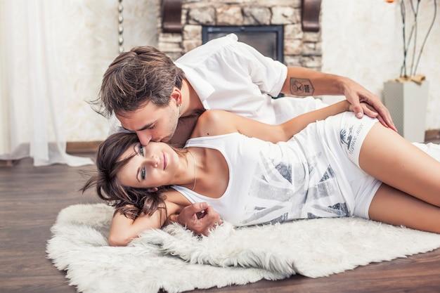 Para mężczyzna i kobieta przytulanie w domu, leżąc na dywanie