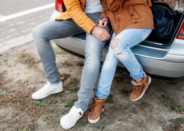 Para mężczyzna i kobieta, ubrani w ciepłe ubrania, siedzący na bagażniku samochodu, przytulający się w zimowy dzień