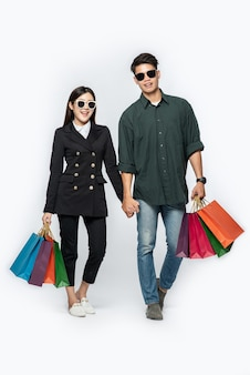 Para mężczyzna i kobieta w okularach i mnóstwo papierowych toreb na zakupy