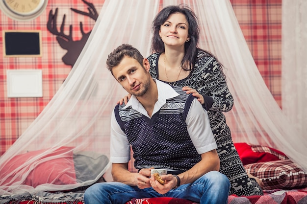 Para mężczyzna i kobieta w sypialni w domu pije herbatę z herbatnikami w czerwonym świątecznym wnętrzu