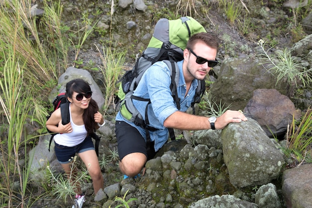 Para mieszanej rasy idzie razem na trekking, idąc pod górę