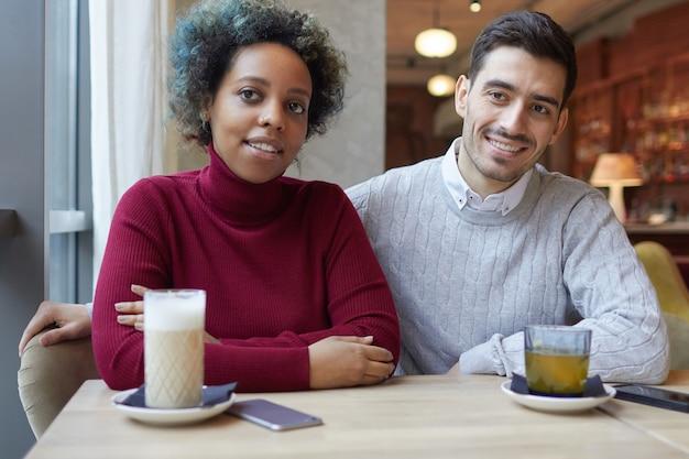 Para mieszanej rasy słucha ciekawą historię swojego przyjaciela w przytulnej kawiarni