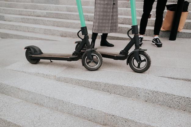 Para miło spędza czas jeżdżąc na skuterach elektrycznych po mieście. koncepcja transportu przyjaznego dla środowiska. nowoczesne technologie. przekrój dwóch hulajnóg elektrycznych oraz nóg kobiety i mężczyzny.