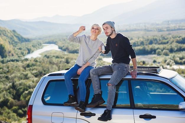Para młoda hipster w miłości pije gorącą kawę lub herbatę siedząc