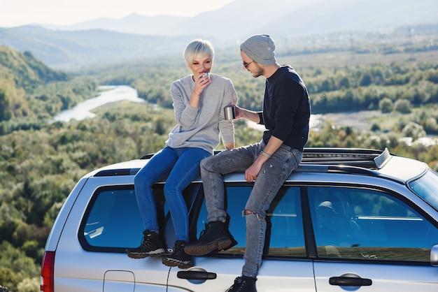 Para młoda hipster w miłości pije gorącą kawę siedząc