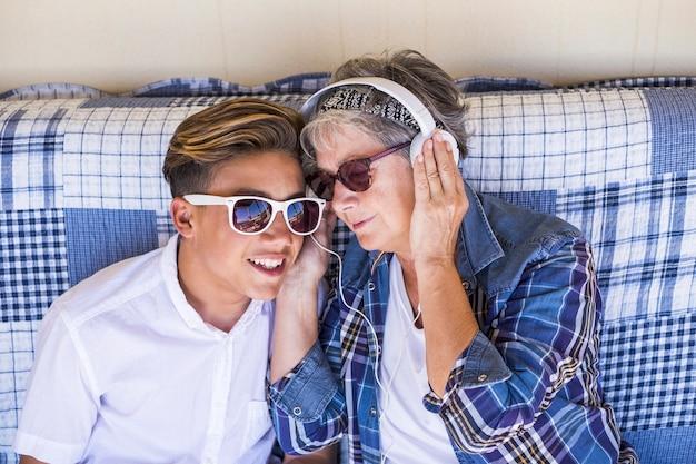 Para młoda i stara babcia i bratanek nastolatka spędzają razem czas z rodziną, słuchają muzyki przez słuchawki i cieszą się dniem