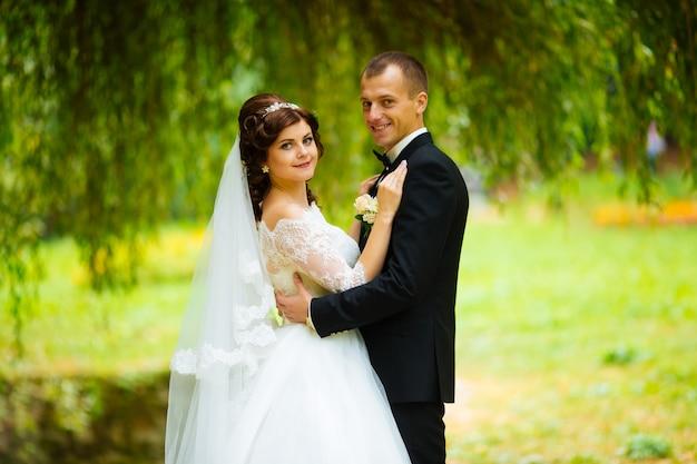 Para młoda. piękna panna młoda i pan młody właśnie wyszłam za mąż. ścieśniać. szczęśliwa panna młoda i pan młody na ich ślub przytulanie. fornal i panna młoda w parku. suknia ślubna. wesele ślubne, jesień
