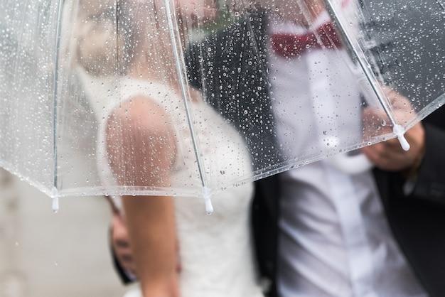 Para młoda w deszczu okryta przezroczystą parasolką, krople deszczu