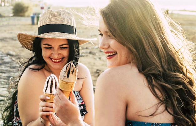 Para młodych kobiet o zaokrąglonych kształtach wspólnie cieszy się lodami i spędzaniem wolnego czasu na świeżym powietrzu
